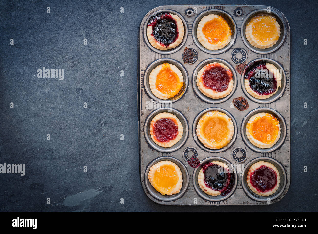 Cooked homemade jam tarts in a baking tray on slate. Vintage filter applied - Stock Image