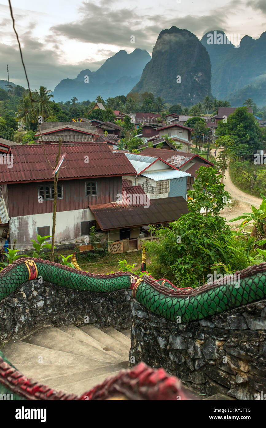 Traditional lao village with temple stairs and mountain background near Vang Vieng, Laos. - Stock Image