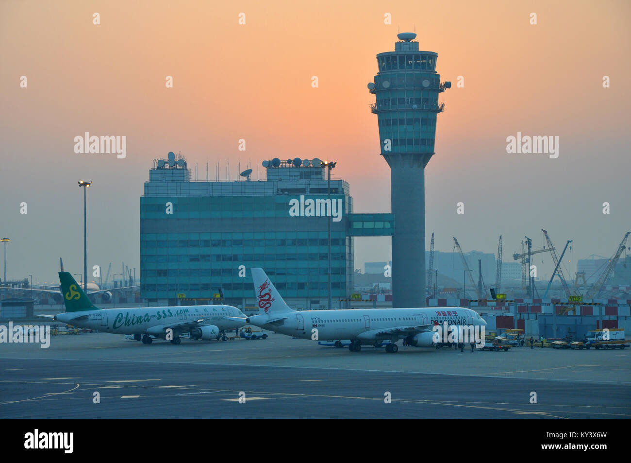 Hong Kong International Airport air traffic control tower with Spring Airlines Airbus A320 200 B-6706 and Dragonair - Stock Image