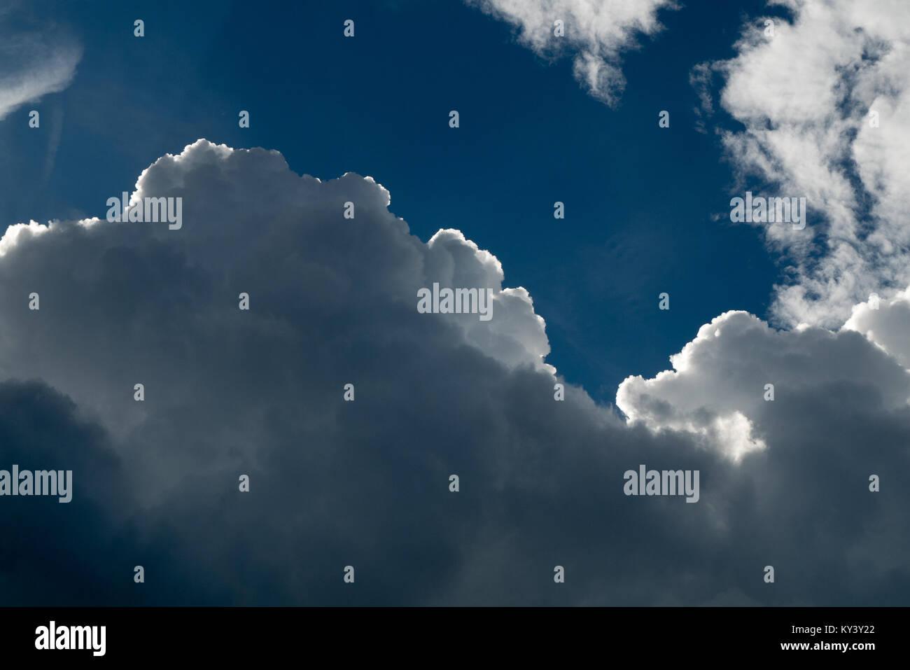 white cumulonimbus on blue sky, dark side of a cloud - Stock Image
