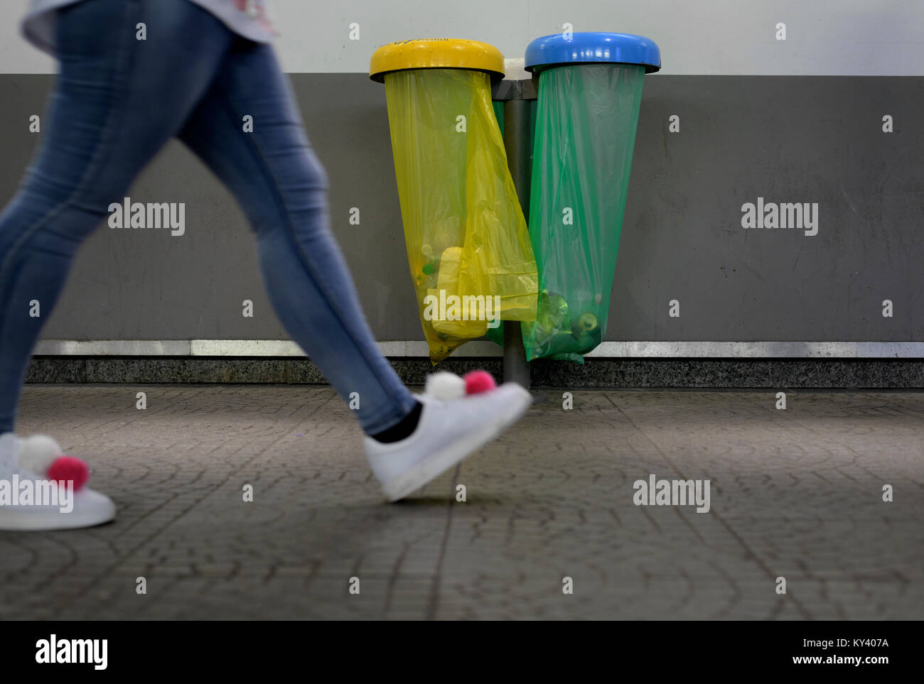 pom poms shoes walks near colored bags of waste - Stock Image