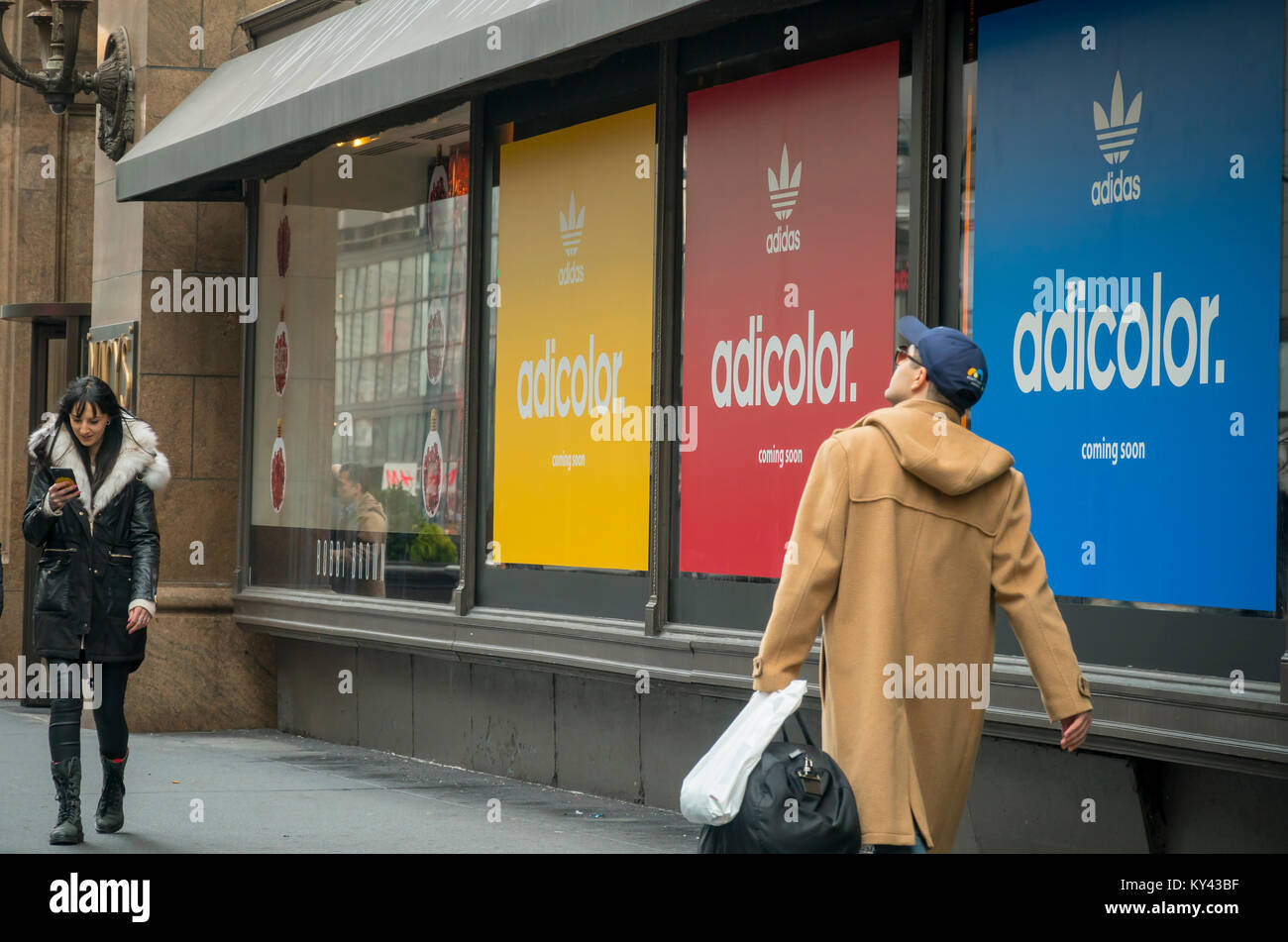 2817239bb45e Shoppers pass by the windows in Macy s Herald Square department store being  prepared for Adidas