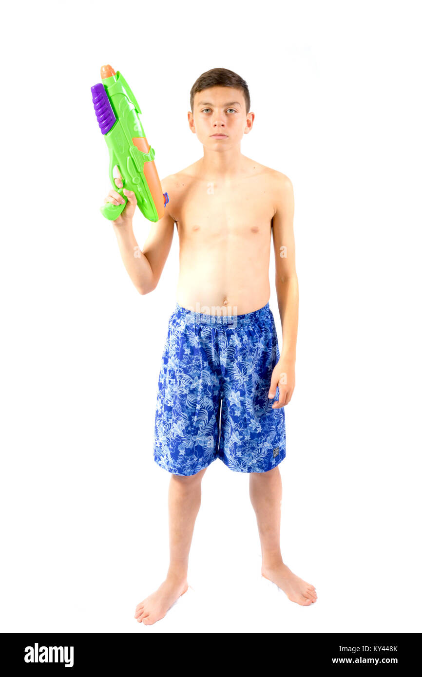 Young teenage boy playing with water guns isolated on a white background - Stock Image
