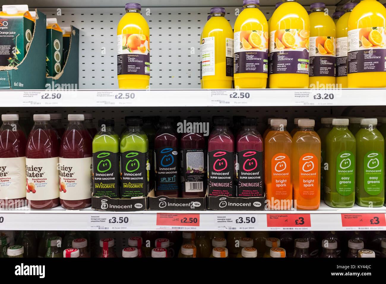 Innocent smoothie and other fruit juices bottles on display on supermarket shelves, UK - Stock Image