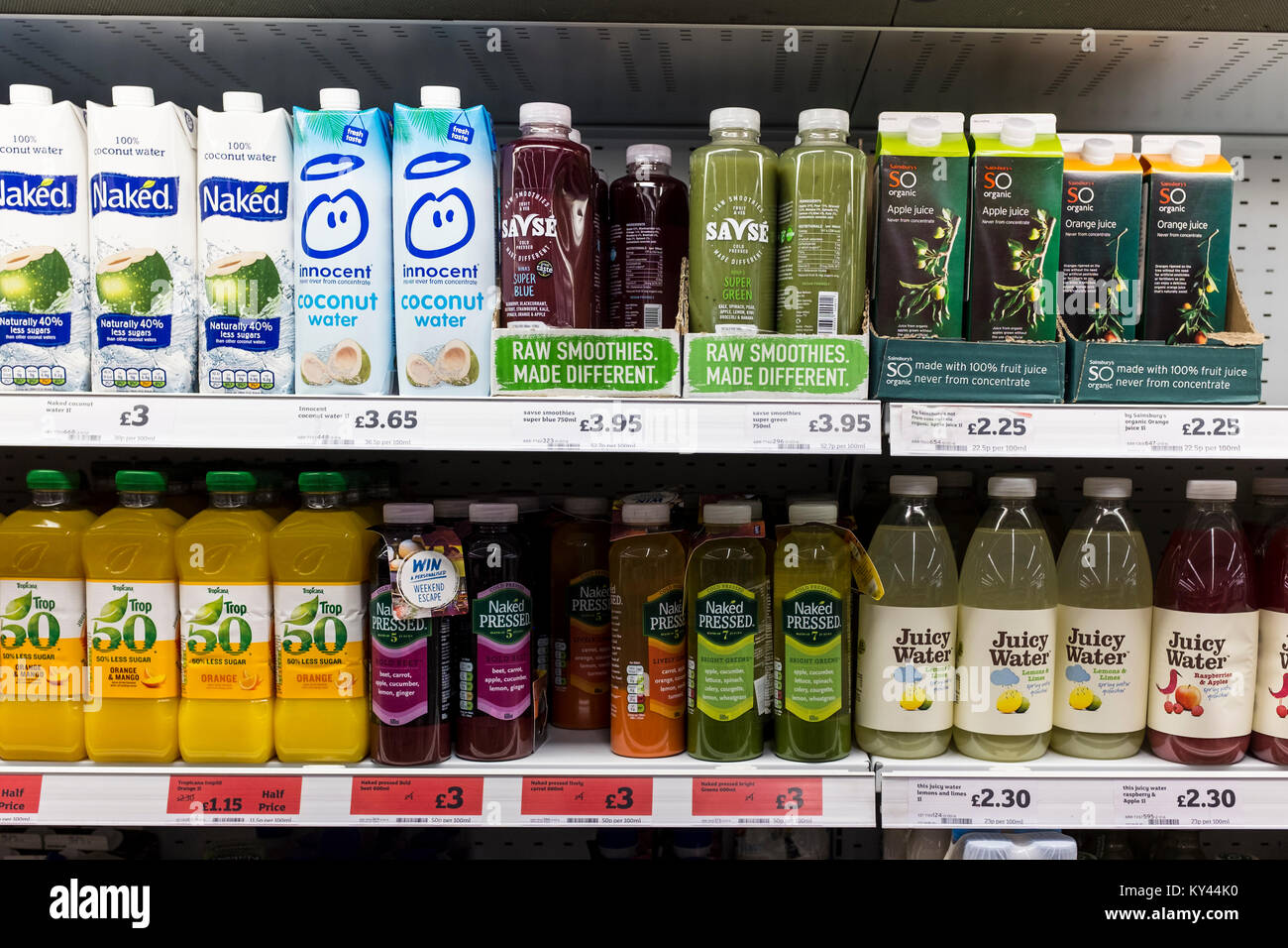 Smoothie and other type of fruit juices bottles on display on supermarket shelves, UK - Stock Image