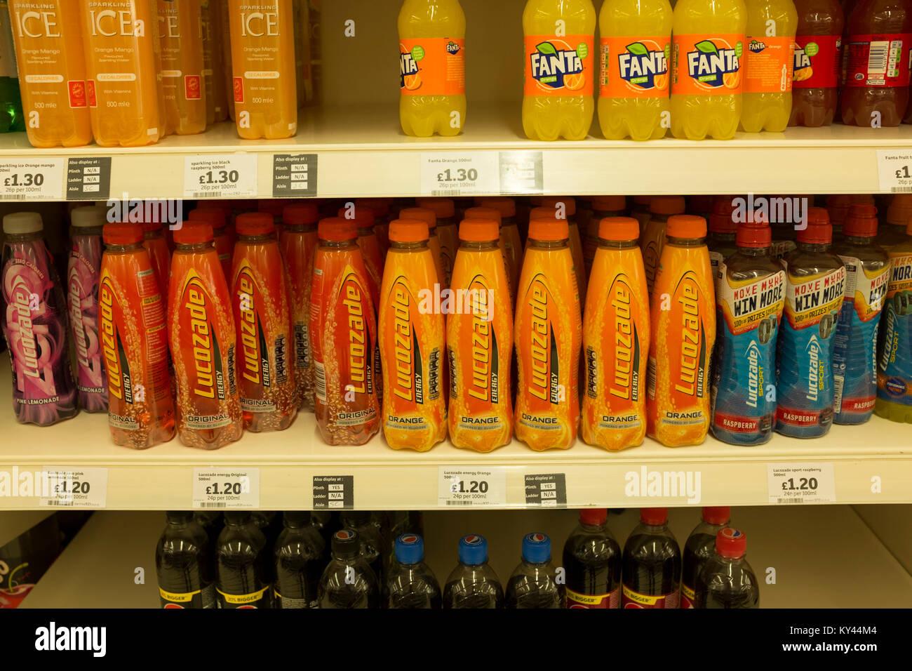 Lucozade Energy drinks bottles on display in supermarket shelves, UK - Stock Image