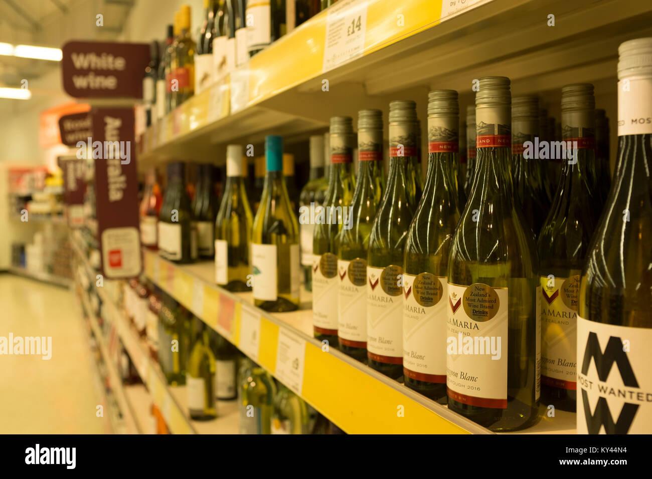 Wine bottles on shelves at Sainsbury's supermarket, UK - Stock Image