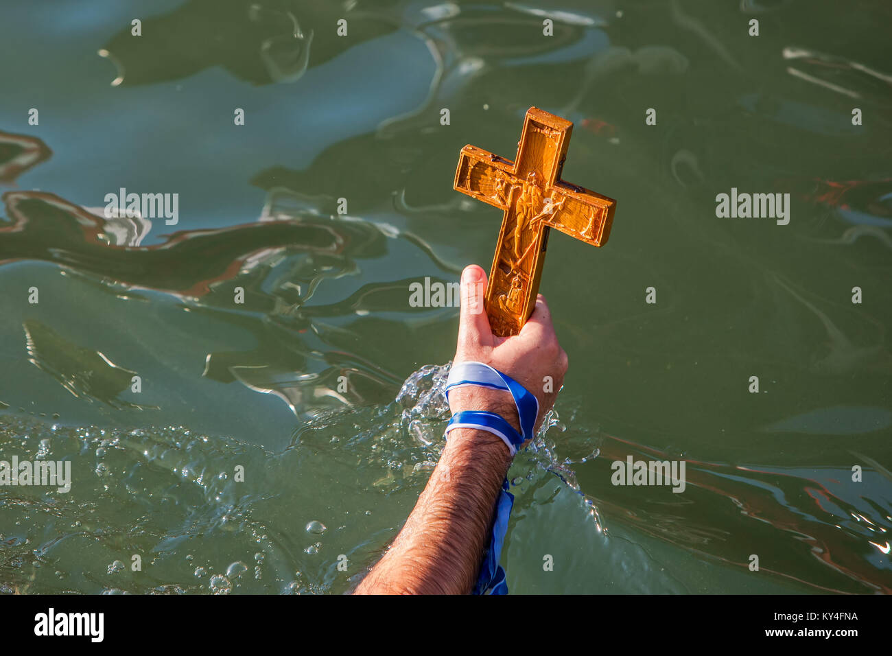 Thessaloniki, January 6, 2018: close-up shot of the hand that retrieves a wooden cross in the sea, at the blessing - Stock Image