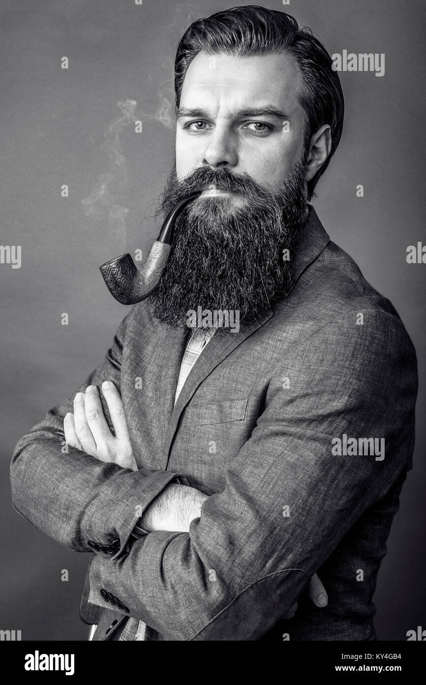 Studio shot of a handsome young man with retro look smoking pipe over gray  background - 514c97ea5623