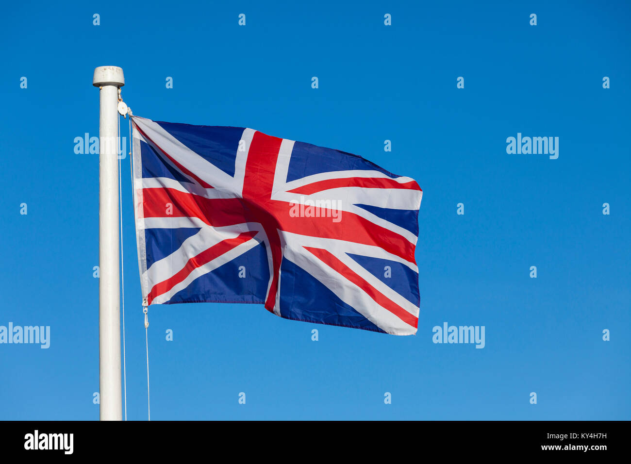 Union Jack flag and flagpole on a bright blue sky background blowing in the wind - Stock Image