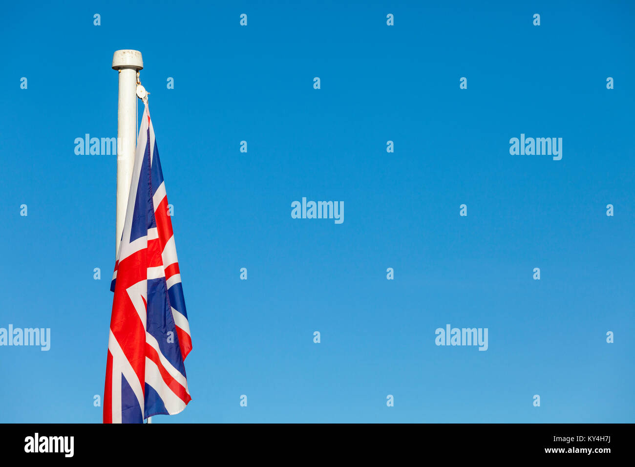 Union Jack flag on a bright blue sky background - Stock Image