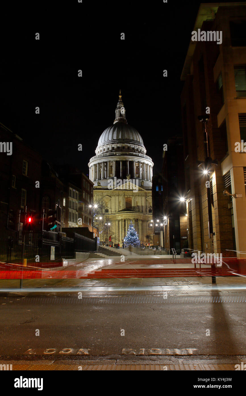 Saint Paul's Cathedral at night looking North from Queen Victoria street, with light trails from passing buses. - Stock Image