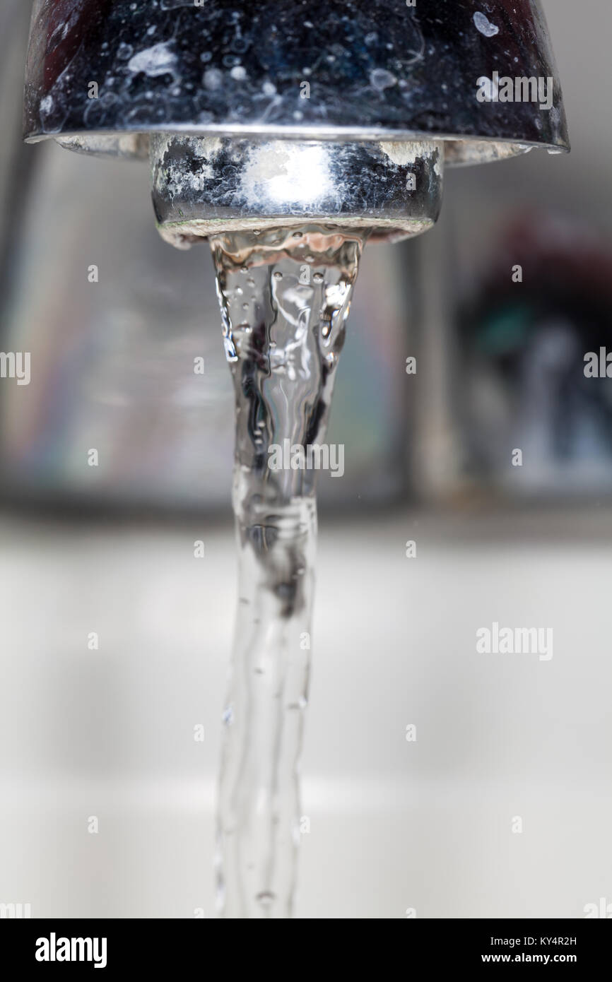 Water running out of a faucet. - Stock Image