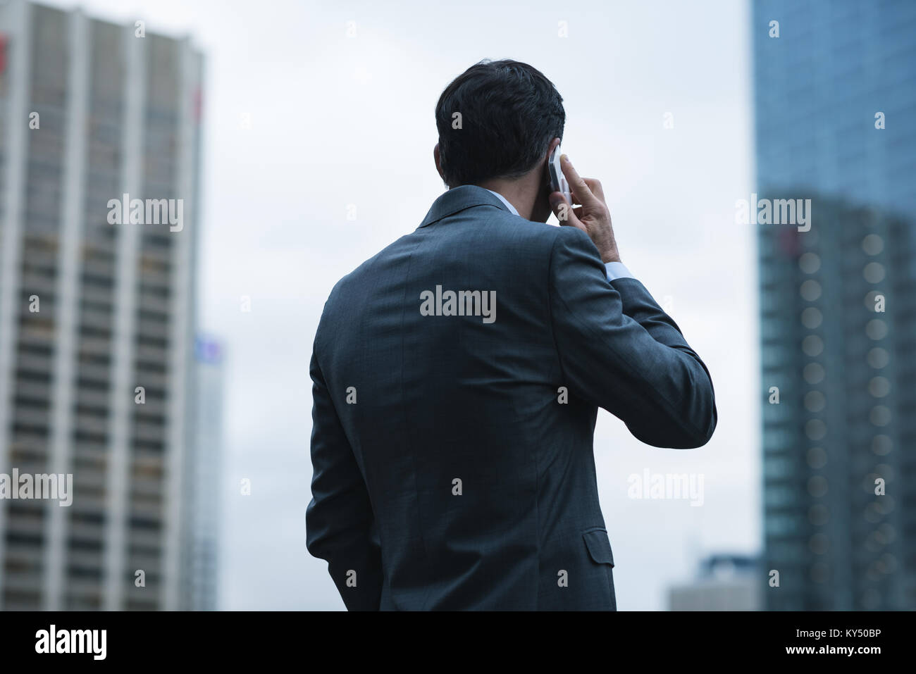 Businessman talking on mobile phone against sky scrapers - Stock Image