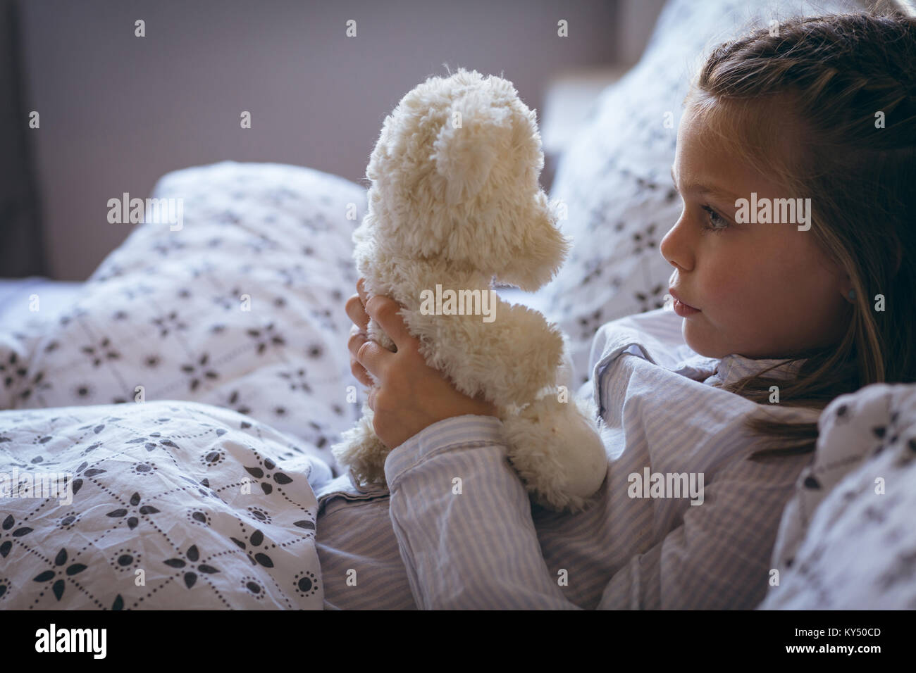 Girl holding teddy bear on bed - Stock Image