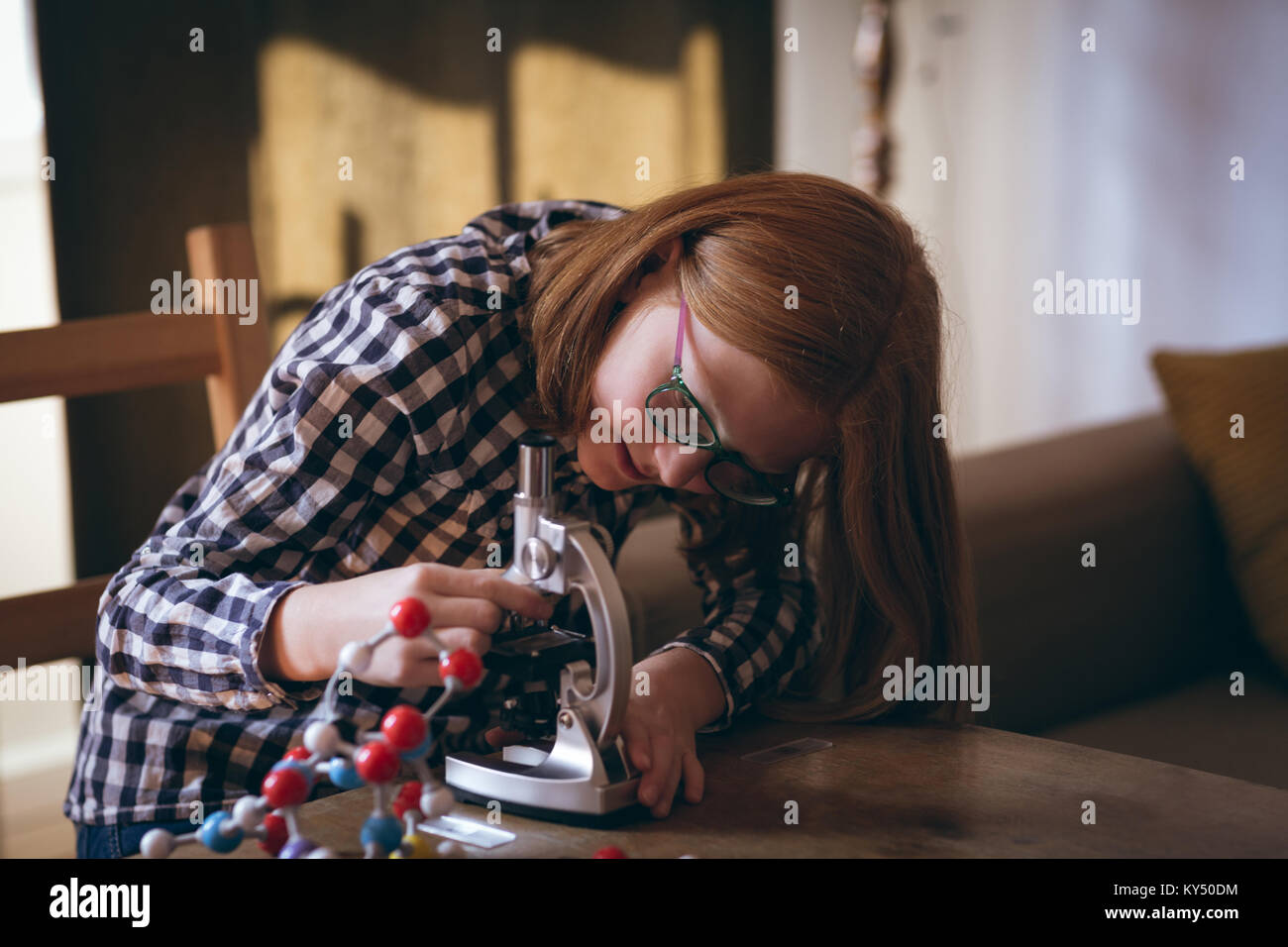 Girl experimenting molecule on microscope - Stock Image