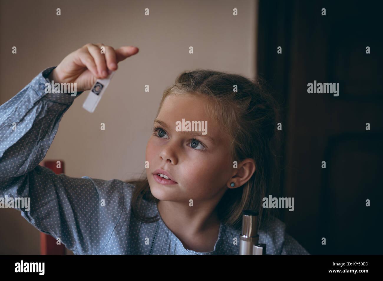 Girl examining the glass slide - Stock Image