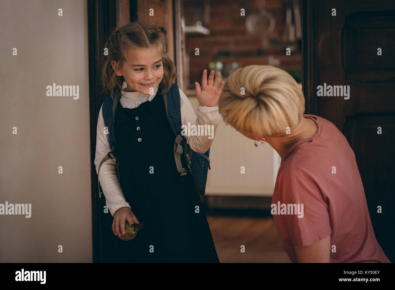 Daughter going to school and saying goodbye to her mother - Stock Image