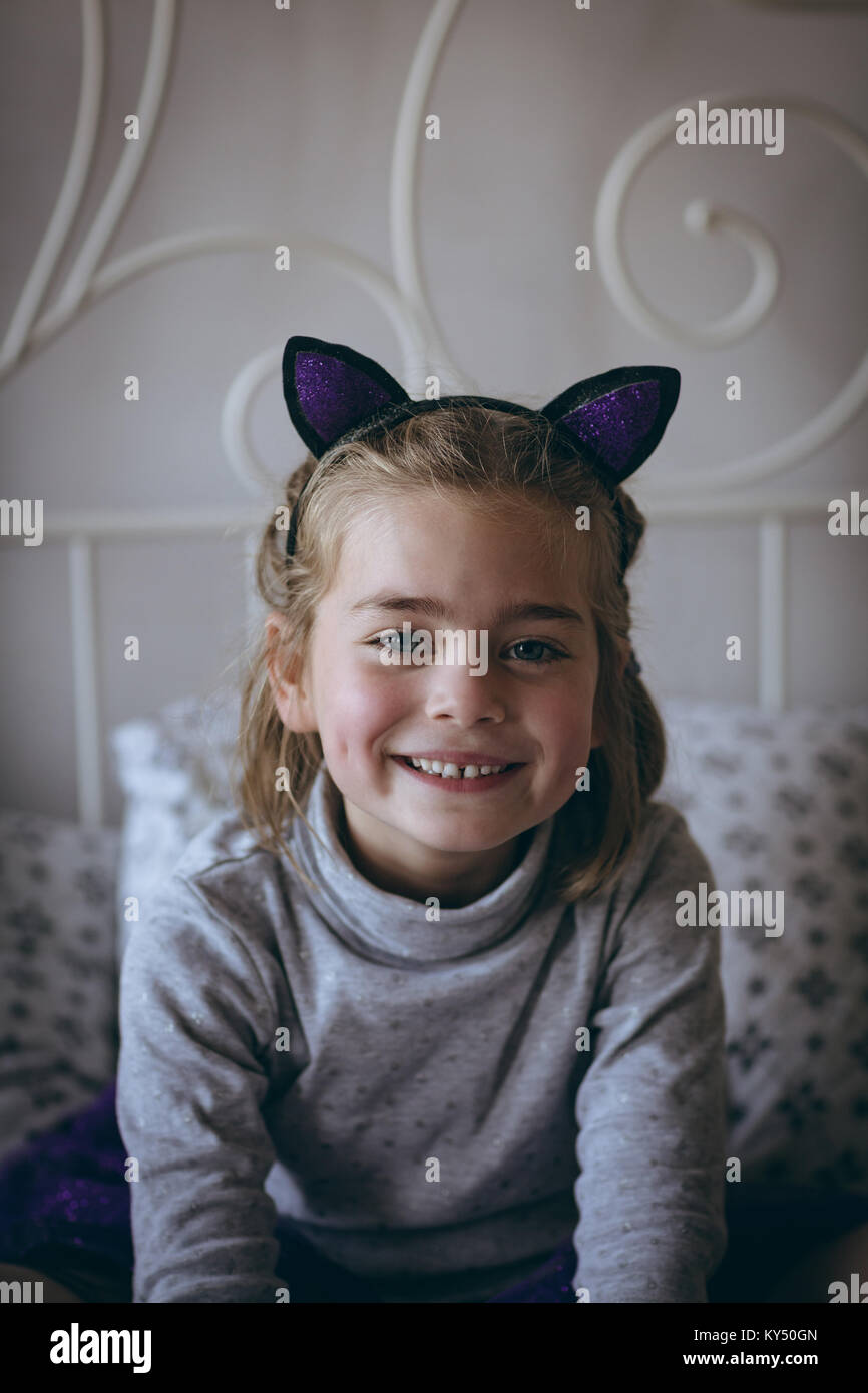 Portrait of smiling girl sitting on bed - Stock Image