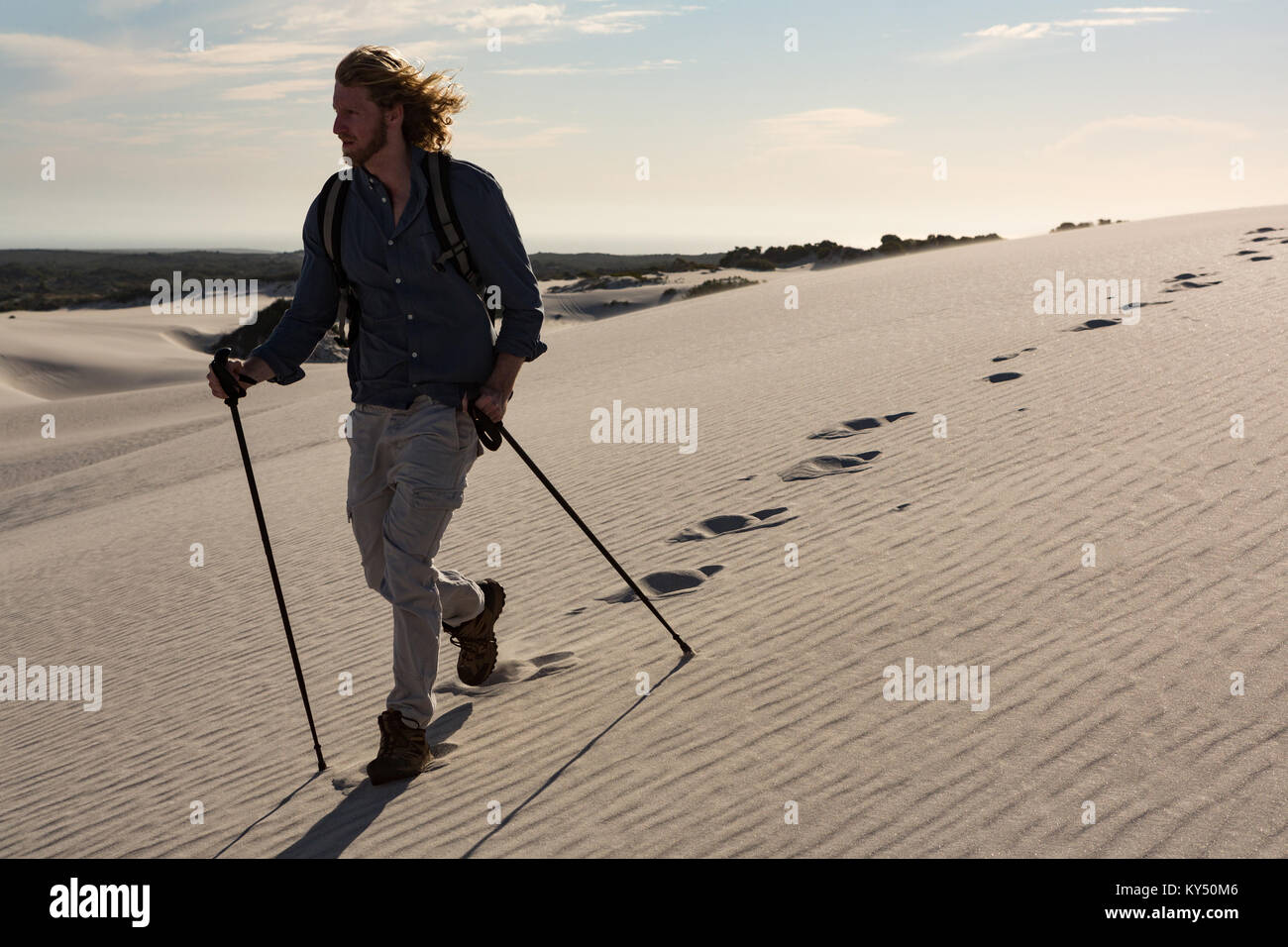 Hiker with trekking pole walking on sand - Stock Image