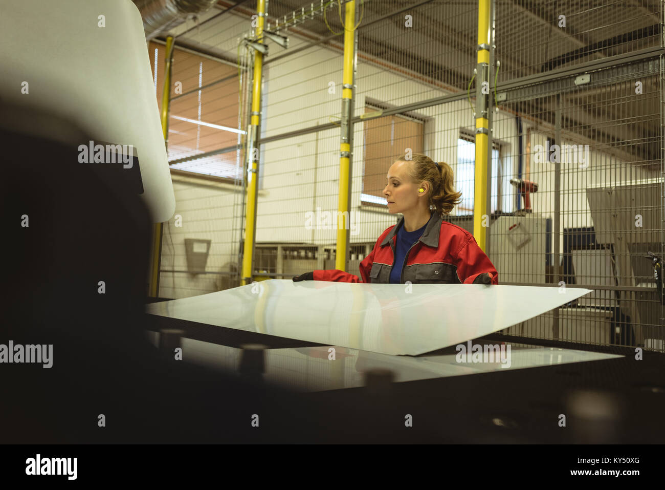 Female worker checking a glass sheet - Stock Image