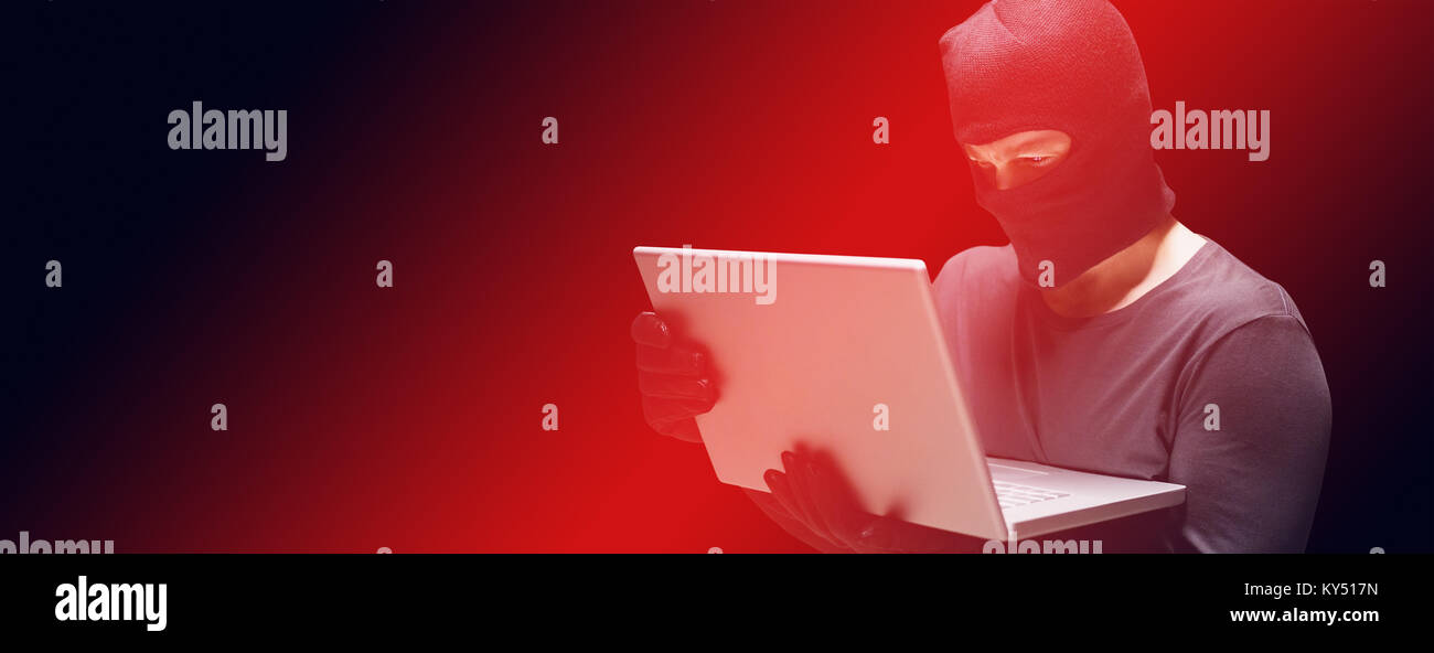 Hacker using laptop to steal identity - Stock Image