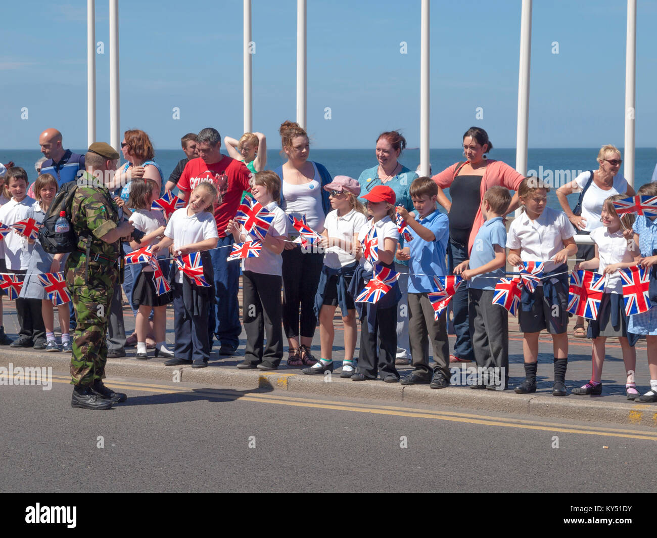 School children with Union Flags meet a soldier at parade of the Yorkshire Regiment marching through Redcar on their - Stock Image