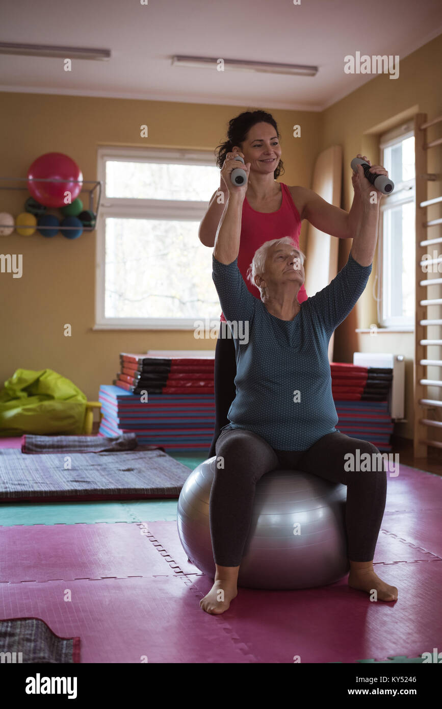 Female therapist assisting senior woman with dumbbells and exercise ball - Stock Image