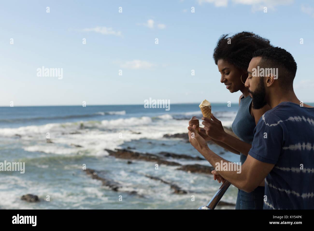 Couple having ice cream near seaside - Stock Image