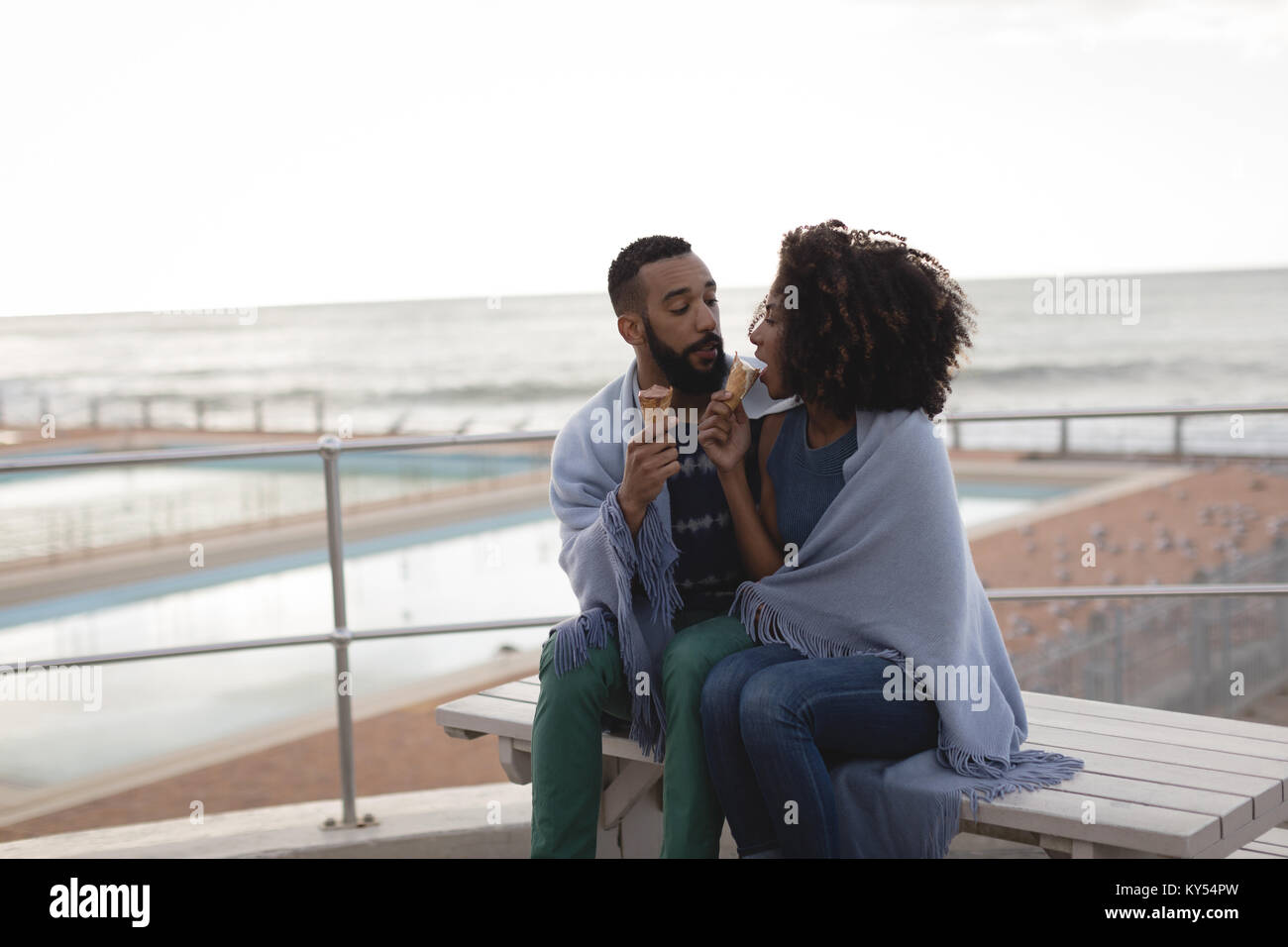Couple wrapped in a shawl having ice cream - Stock Image