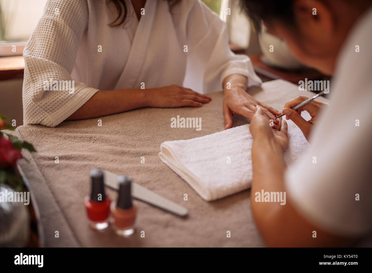 Woman getting her nails done by a manicurist in a beauty salon ...