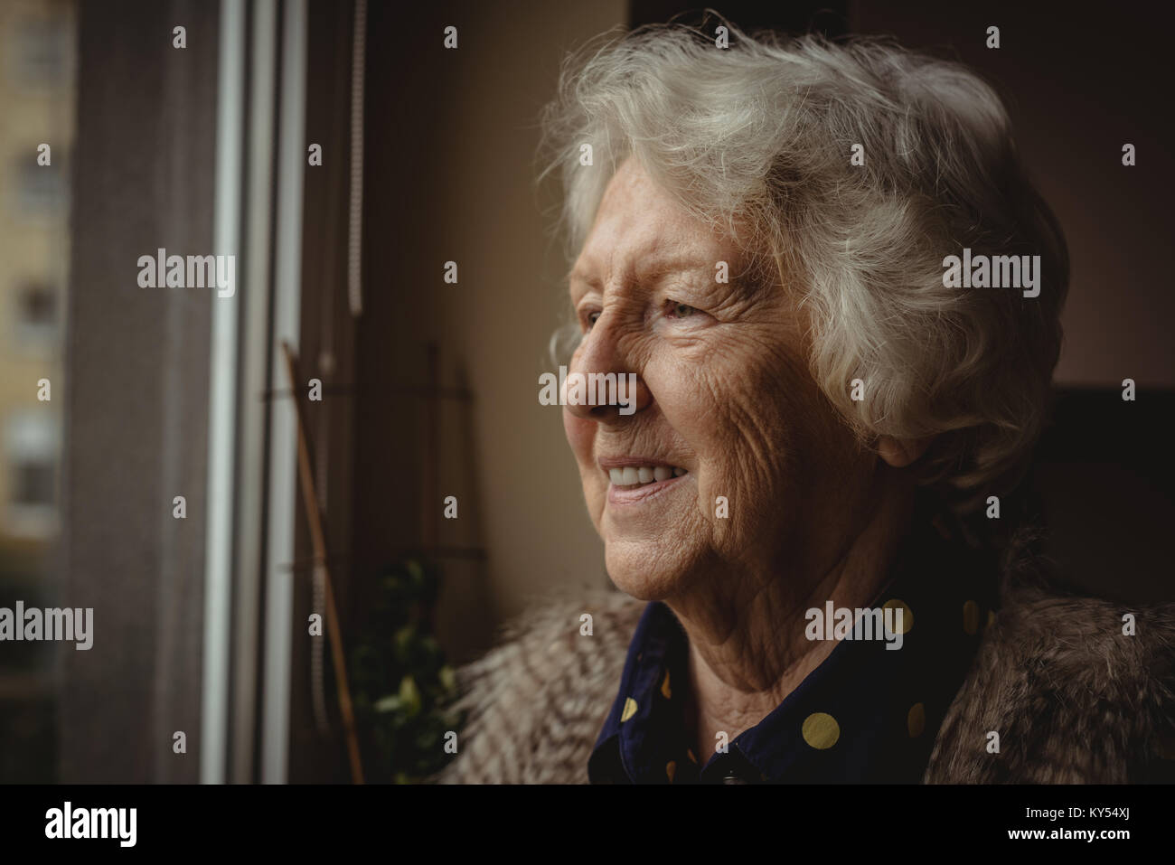 Smiling senior woman looking out of the window - Stock Image