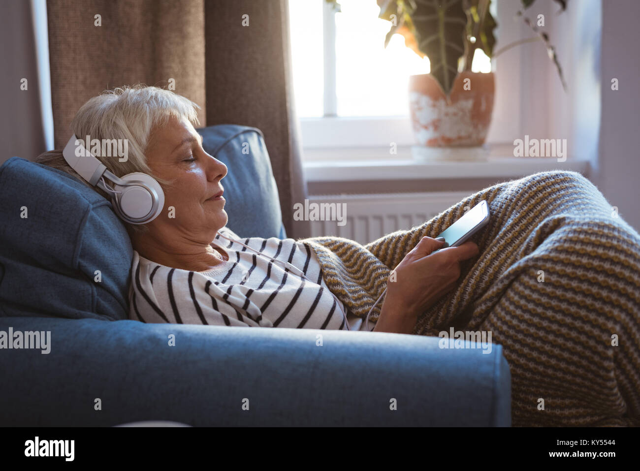 Senior woman listing to music on phone while siting on sofa in living room - Stock Image
