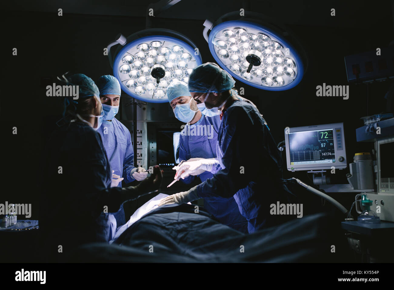 Medical team performing surgery in hospital. Group of surgeons at work in operation theater. - Stock Image