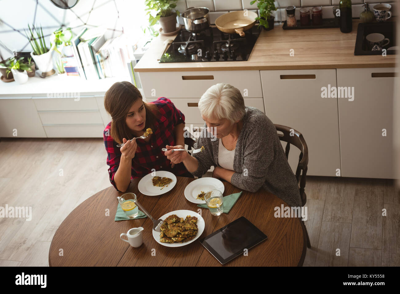 Senior woman and daughter eating omelet in the kitchen for breakfast - Stock Image
