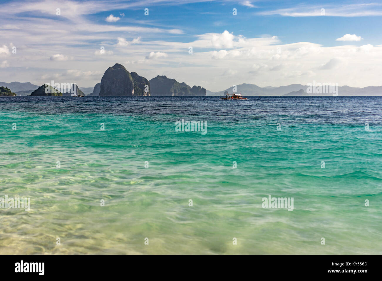 Small islands sat on the horizon taken at a low angle over an empty calm tropical sea  with depth of field. - Stock Image