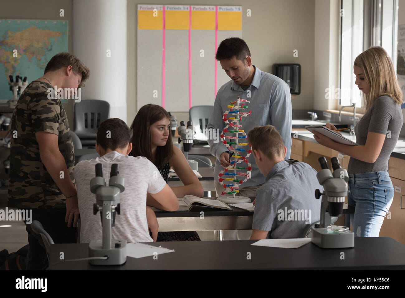 Teacher assisting students in experiment on molecule Stock Photo
