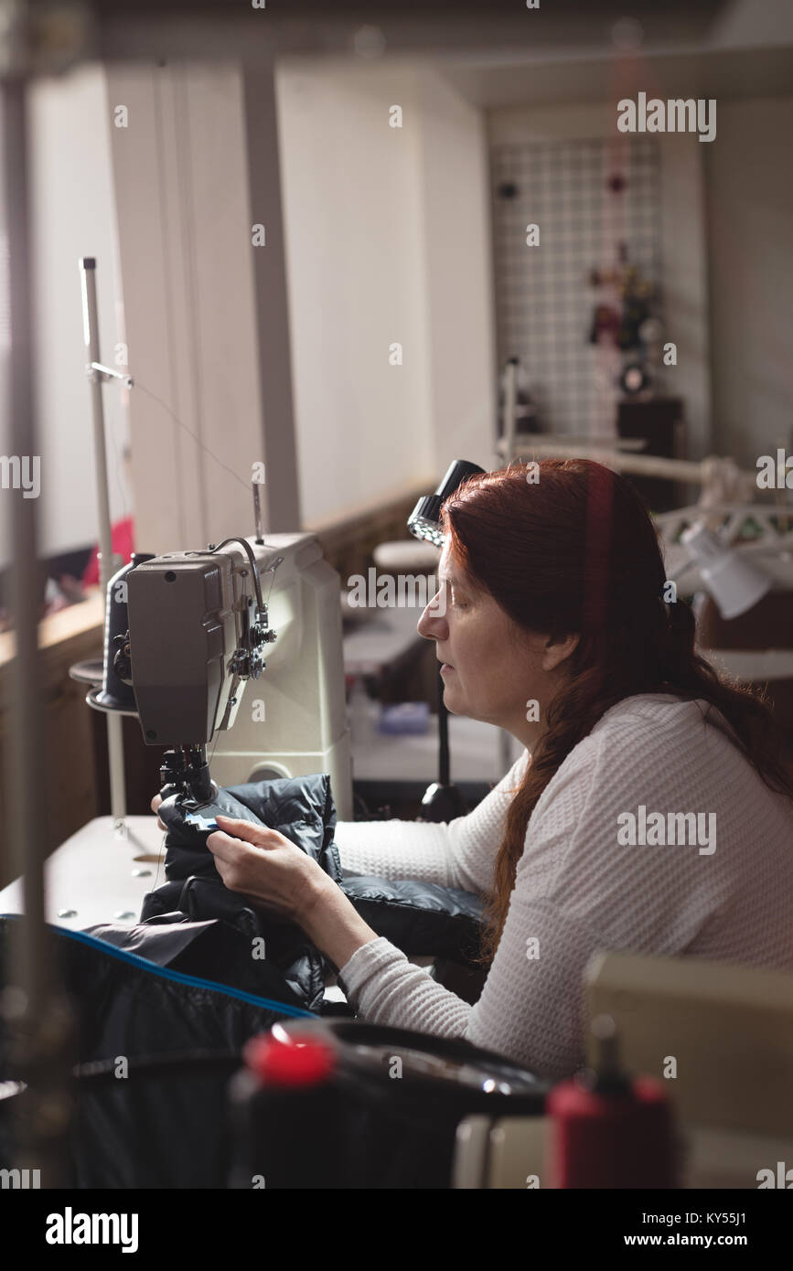 Tailor sewing cloth with sewing machine - Stock Image
