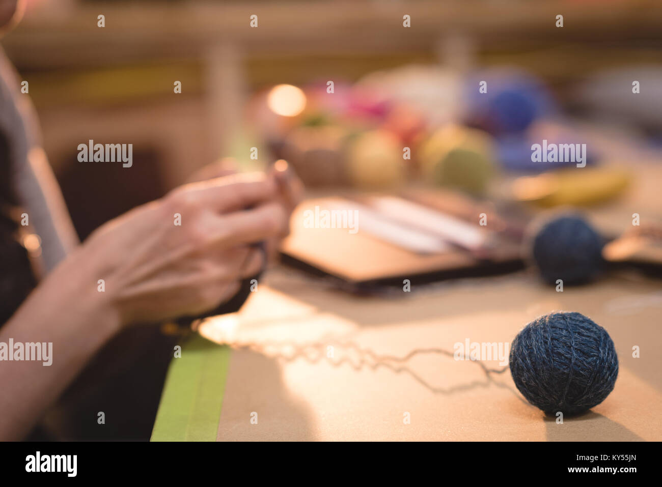 Woman knitting wool at tailor shop - Stock Image