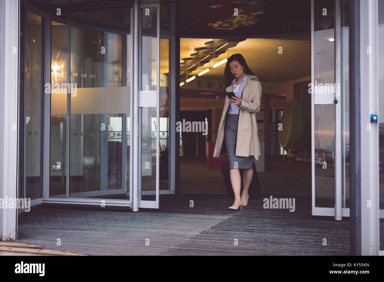 Businesswoman using mobile phone while walking out of the hotel Stock Photo