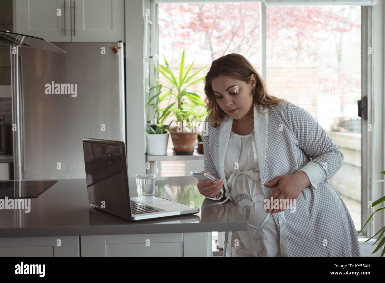 Pregnant woman using mobile phone - Stock Image