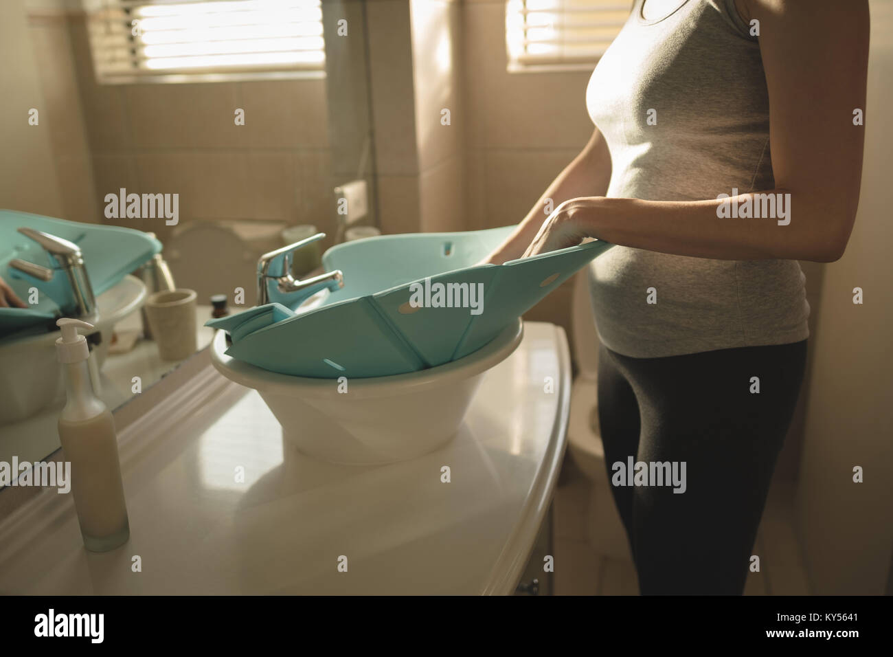 Young mom placing baby bath seat into bathroom sink - Stock Image