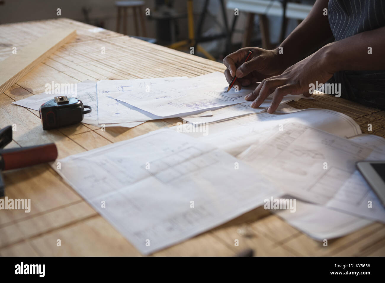 Mid section of carpenter working at table - Stock Image