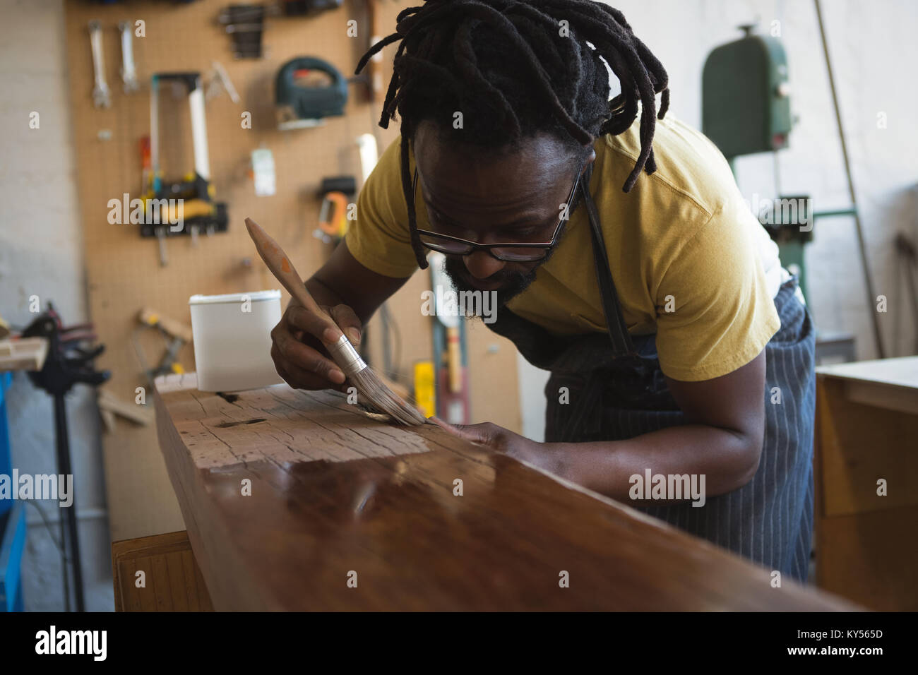 Carpenter painting wooden plank - Stock Image