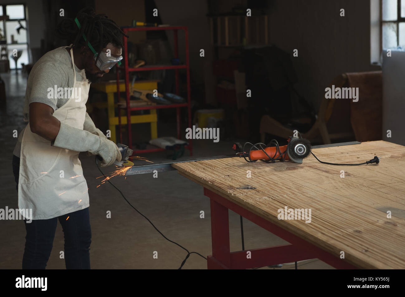Carpenter cutting metal with electric saw Stock Photo