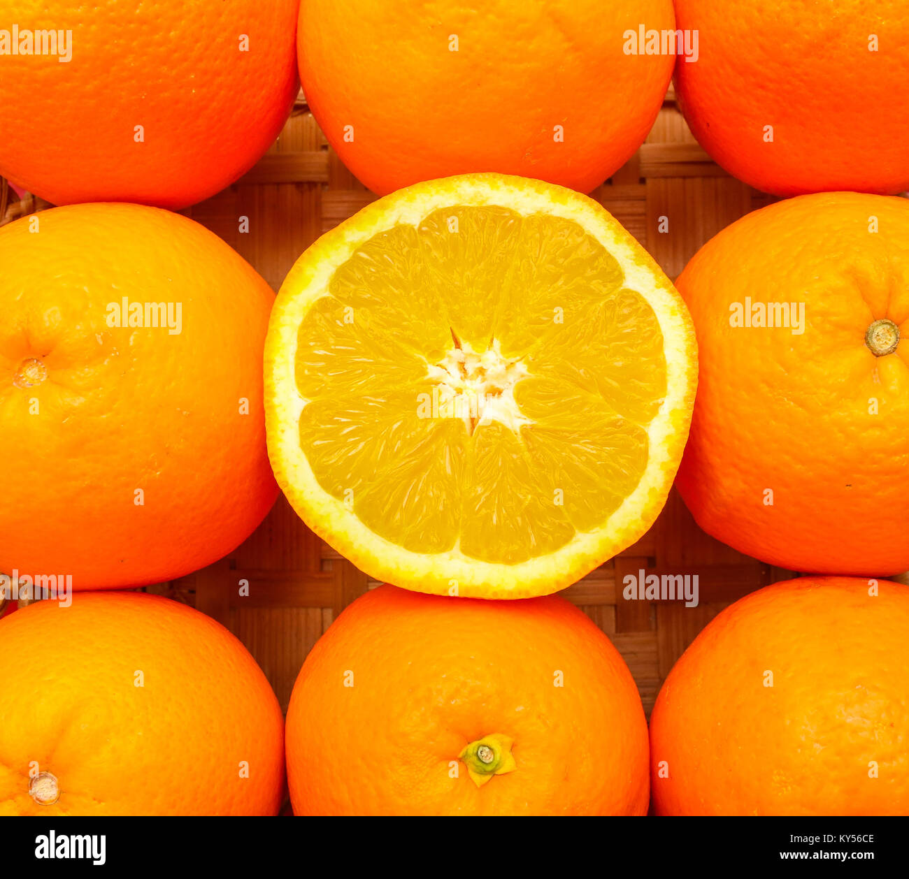 Half of an fresh orange in middle of other oranges - Stock Image