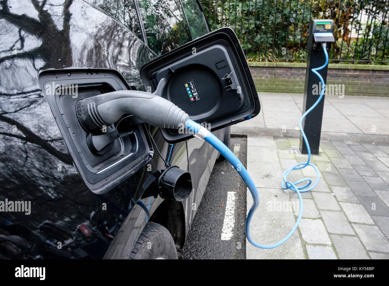Electric car at public charging point in central London, UK - Stock Image