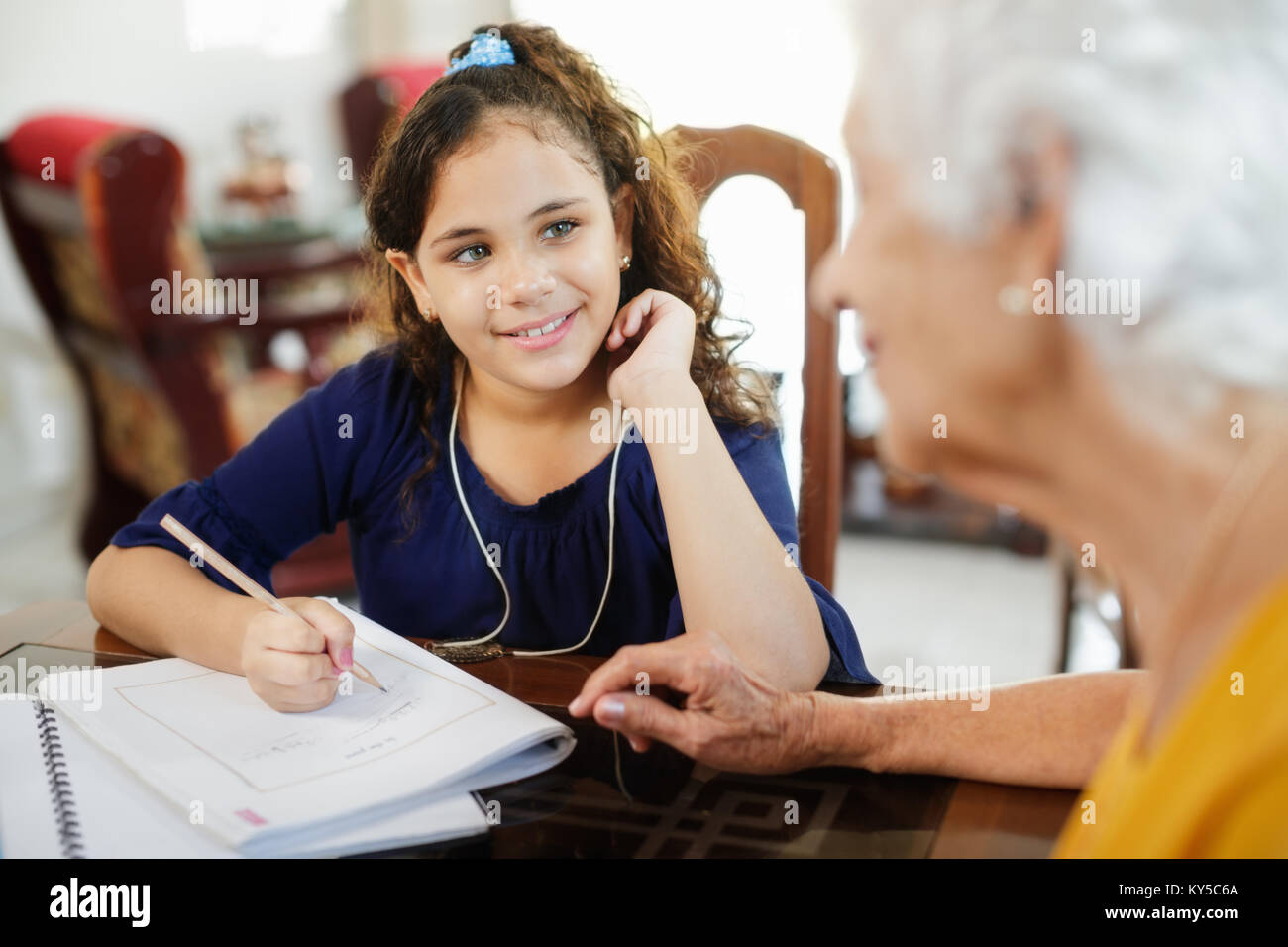 Happy little girl doing school homework with elderly woman at home. Family relationship with grandmother and granddaughter. Stock Photo
