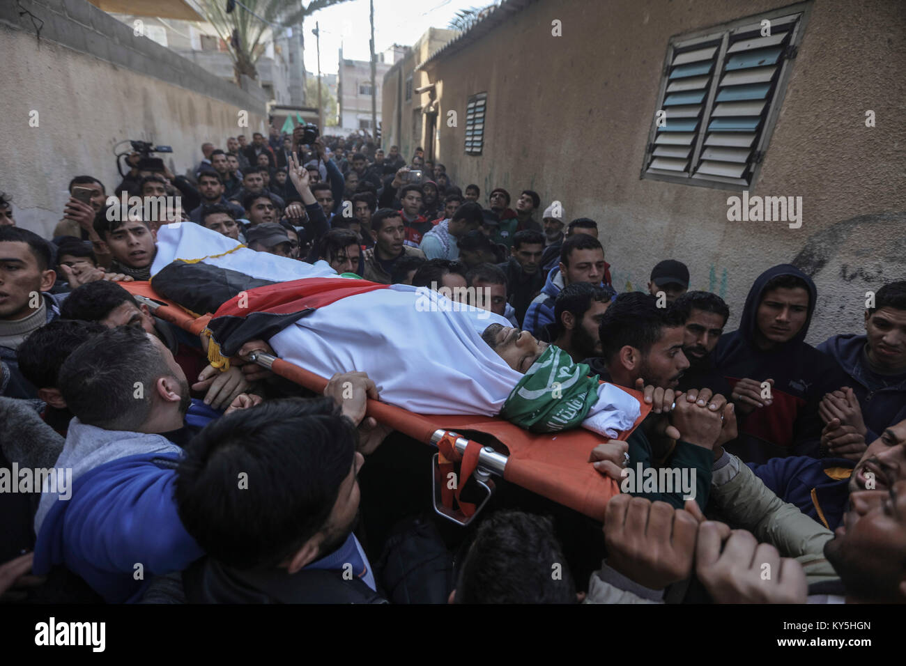Relatives and mourners carry the body of 32-year-old Palestinian fisherman Abdullah Ramadan Zidan, during his funeral - Stock Image