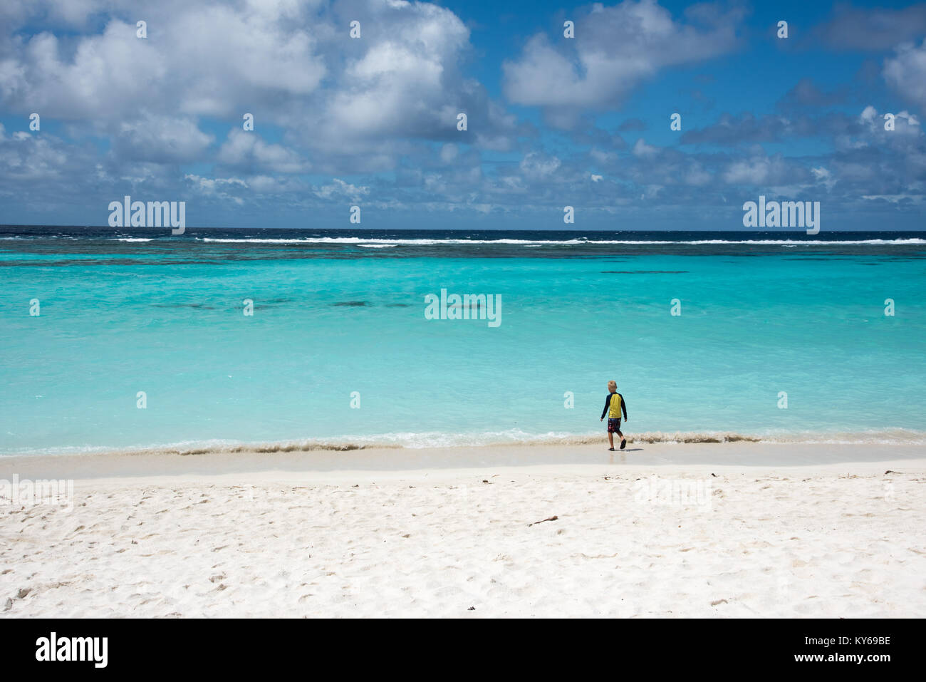 TADINE,MARE,NEW CALEDONIA-DECEMBER 3,2016: Young boy walking to the Pacific Ocean waters at Yejele Beach in Mare, - Stock Image